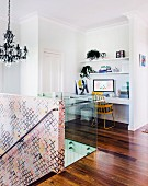 Desk and retro chair in niche, glass balustrade and staircase wall covered in wallpaper with graphic pattern