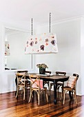 Bentwood chairs with crossed backrests around dining table below floral pendant lamp next to large mirror on wall