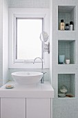 Modern washstand below window and fitted shelf niches with mosaic tiles in bright bathroom