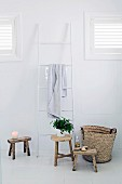 Still-life arrangement of ladder-style towel rail, wooden stools and basket in white bathroom