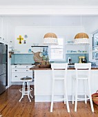 Island counter, bar stools and two paint-dipped wicker pendant lamps in modern kitchen