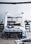 Rustic bed with canopy made of white fabric, former door frame as bed headboard