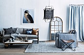 Rustic coffee table with wheels in front of sofa, armchair with gray cover and stool