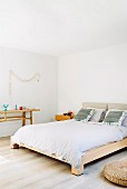 Pale wooden furniture and white wall in purist bedroom