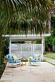 Two armchairs and a side table on a terrace in the palm garden of a beach house