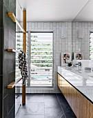 Einbauwaschtisch und Holzelement mit Stangen für Handtücher in modernem Designerbad mit anthrazitfarbenen Fliesen