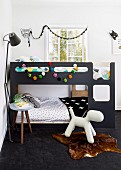 Children's bedroom in charcoal grey with colourful garland of pompoms on bunk beds and dog figurine on animal-skin rug