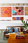 A gallery of colorful pictures over a wooden sofa bench with colorful pillows