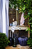 Improvised shower area in garden with wicker hurdle screen and blue planters on floor