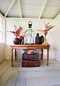 Candle lantern and vessels with branches on tropical wooden table, vintage suitcase on the white patinated wooden floor