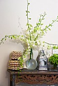 Magnificent orchid branches in a glass vase, tins with shell decoration and handcrafted lantern on a Balinese console table