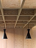 Retro pendant lamps with black metal lampshades suspended from modern coffered ceiling in pale wood