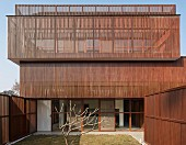 Facade of modern, Indian house with sunscreens and fences made from delicate wooden elements