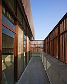 Narrow balcony of modern, Indian house with facade screened from sun by slim wooden slats