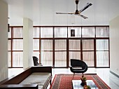 Seating area with retro leather armchairs and purist wooden sofa on Oriental rug; subdued light falling through glass wall with vertical, slatted sun screens