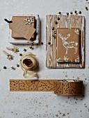 In Papier mit hellbraun-weißem Motivdruck verpackte Weihnachtsgeschenke und passende Bänder auf Geschenkpapier-Hintergrund