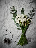 Bouquet of white flowers tied with decorative black and white cord on crumpled paper