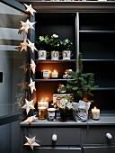 Kerzen, Blumenschmuck und Leuchtgirlande mit Sternen, arrangiert auf dunkelgrauem Buffet