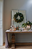 Festive arrangement for Christmas buffet on antique table below wreath of leaves on wall