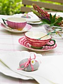 Pebble with ribbon and flower used as napkin weight on summery table set for afternoon tea
