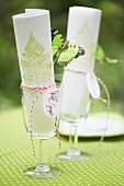 Paper napkins hand-stamped with fern motifs in wine glasses