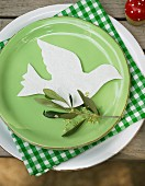 A dove on white, handmade paper with an olive sprig on a green plate