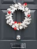 Wreath of white paper with red bells and fabric birds on front door