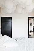Double bed with white bed linen below a sea of paper lanterns on ceiling; black-painted interior door in background