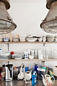 Detail of kitchen; crockery on wooden shelves, utensils on stainless steel worksurface and industrial-style pendant lamps