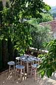 Wooden stools at round table on rustic terrace under lemon tree