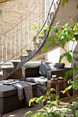 Wicker armchair with grey cushions incourtyard seating area below curved exterior staircase
