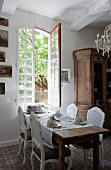 Rococo chairs around set table in front of open window next to old farmhouse cupboard in rustic dining room