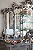Antique dresser with buffet arranged in front of mirror