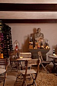 Folding wooden chairs around bistro table in front of stone bust on antique console table and wine rack in cellar-style room