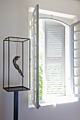 Suspended figurine in glass case on metal stand next to lattice window with white interior shutters