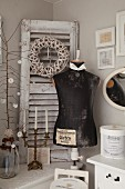 Vintage tailors' dummy and candelabra in front of wreath on detached window shutter