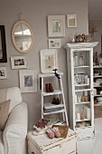 Shabby-chic occasional table below pictures hung on pastel wall