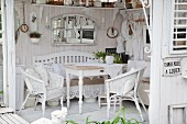 Wooden table and white wicker chairs in shabby-chic summer house with white wooden floor