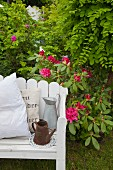 Jugs and cushions on white-painted bench in front of flowering rhododendron