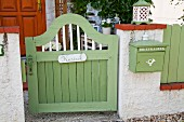Green-painted wooden garden gate with name plate next to matching letterbox mounted on wall