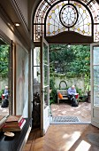 Open double glass doors with Art Nouveau fanlight and view of elderly man and dog in summery courtyard