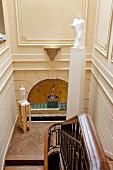 Blick von oben auf Treppenlauf und Podest, Skulptur auf Stele vor Jugendstil Wand mit vergoldetem Rundbogen