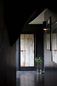 Dunkel gestrichener Flur mit einer alten Holztür