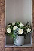 Strauß weiße Rosen in einem Regalfach mit Holzrahmen