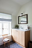 Washstand with wooden base unit and marble counter in attic bathroom