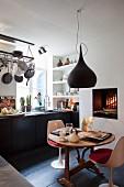 Essplatz mit weißen Klassikerstühlen unter schwarzer Pendelleuchte vor Küchenzeile in eklektischem Ambiente mit offenem Kaminfeuer und Grilleinsatz