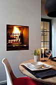 Weißer Klassikerstuhl an rustikalem Holztischisch mit elegantem Gedeck, offenes Kaminfeuer mit Grilleinsatz