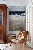 Klassikersessel mit Kuhfell-Bezug in Zimmerecke vor Sprossentür, an Wand Gemälde