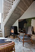 50s-style chair on herringbone stone floor and log burner below concrete staircase with perforated brick side wall