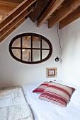 Bed in corner of room below oval transom window